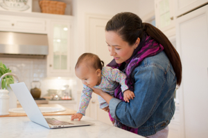 Woman looking at laptop while holding young child at home